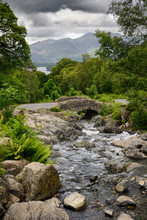 Old Stone Ashness Bridge Over Barrow Beck Flowing To Derwentwater Lake And Keswick Under Skiddaw Mountain Lake District England