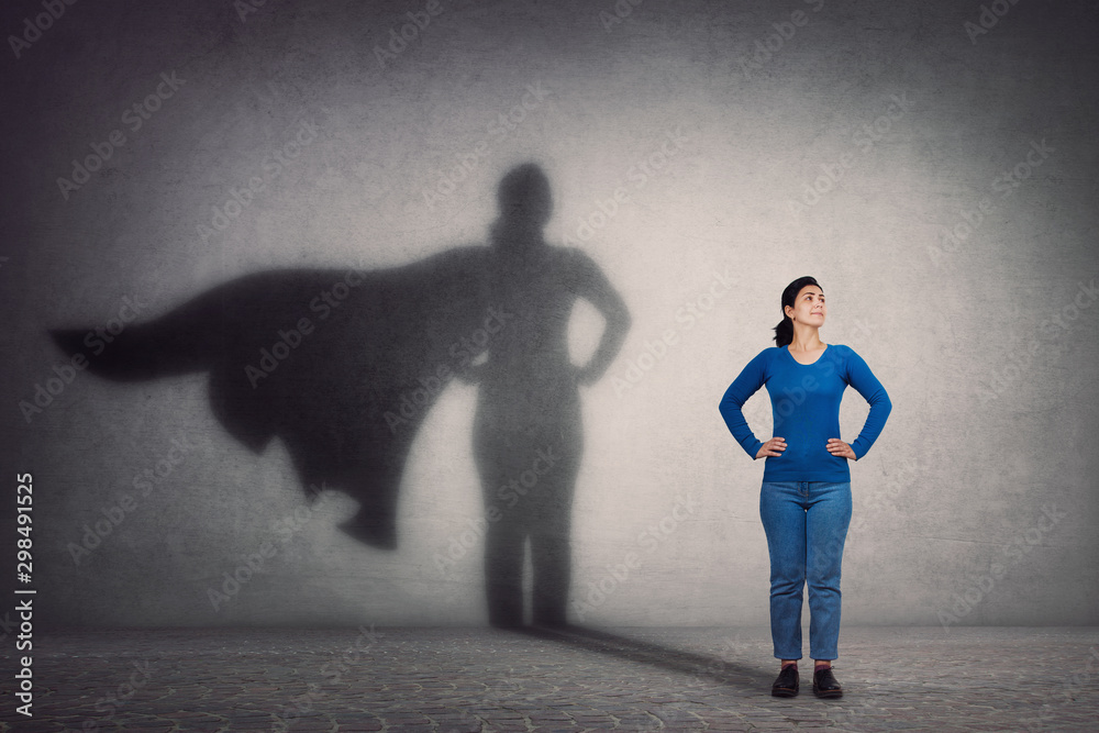 Fototapeta Brave woman keeps arms on hips, smiling confident, casting a superhero with cape shadow on the wall. Ambition and business success concept. Leadership hero power, motivation and inner strength symbol.