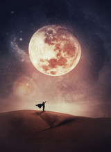 Surreal Scene With A Woman Hero Silhouette With Cape On The Top Of A Hill Raises Hand Up To The Sky Watching The Full Moon Night. Mystic Night View.