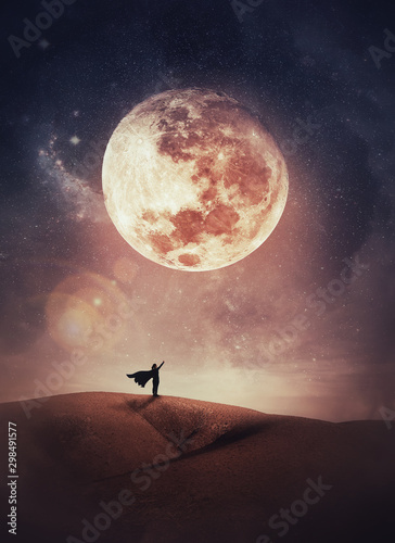 Fotografía Surreal scene with a woman hero silhouette with cape on the top of a hill raises hand up to the sky watching the full moon night