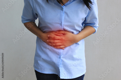 Photo Young woman feeling pain with her stomachache on white background, Healthcare an