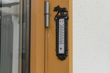 Close Up View Of Outdoor Thermometer On Yellow Wooden Pillar. Beautiful Autumn Day Backgrounds.