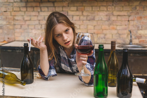 Fototapeta Young sad and wasted alcoholic woman sitting at kitchen couch drinking red wine and smoking, completely drunk looking depressed lonely and suffering hangover in alcoholism and alcohol abuse