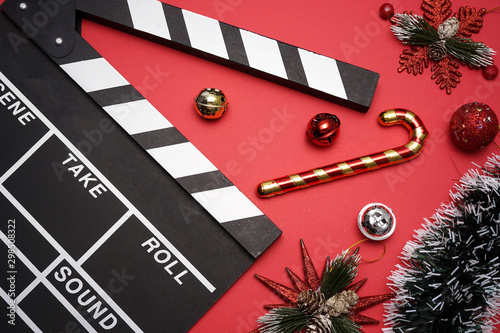 Valokuva  Filmmaker clapperboard with christmas decorations on red background