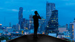 Businessman standing using smart phone on open roof top balcony watching city night view.Business with ambition and vision concept.