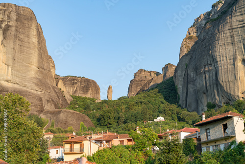 Valokuvatapetti Houses and church in foothills among trees below towering rocks and pinnacles at Meteora