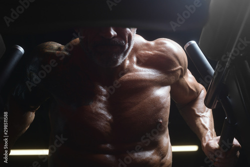 Handsome athletic men pumping up muscles push-ups on uneven bars workout fitness Fototapet