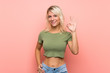 Leinwandbild Motiv Young blonde woman over isolated pink background showing ok sign with fingers