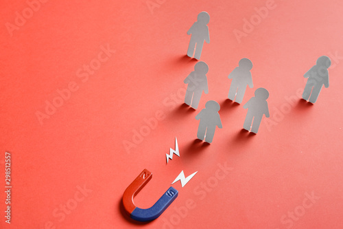Cuadros en Lienzo Magnet attracting paper people on red background, space for text