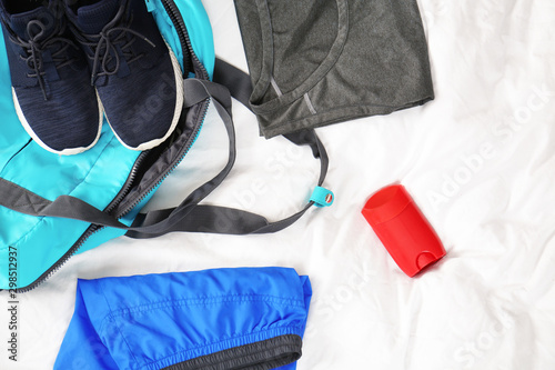Photo Deodorant and gym clothes on white fabric, top view