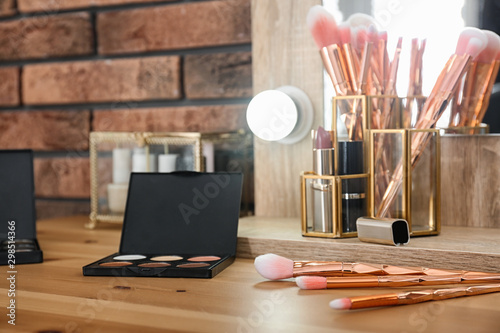 Fotografía Cosmetic and brushes on dressing table in makeup room