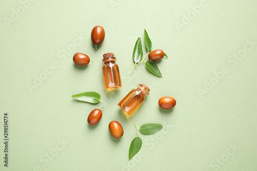 Fototapeta Glass bottles with jojoba oil and seeds on green background, flat lay obraz