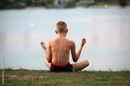 Fotografia  A young boy practices focus on water by practicing yoga