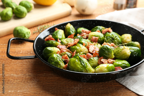 Photo Tasty roasted Brussels sprouts with bacon on wooden table, closeup