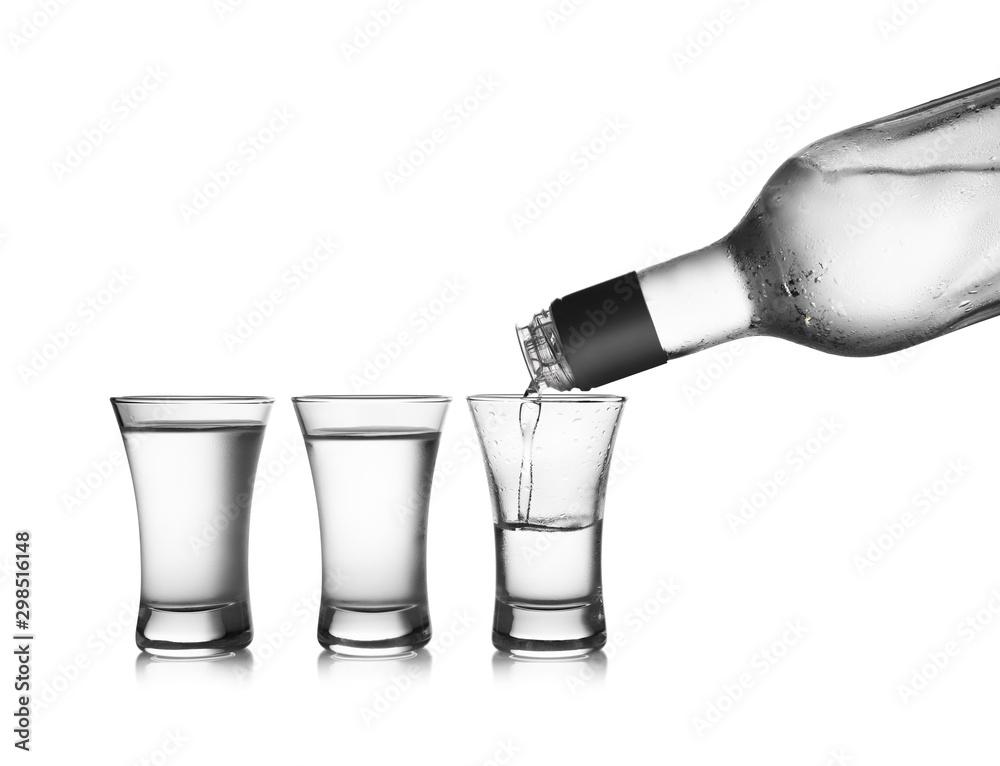 Fototapeta Pouring cold vodka into shot glass on white background