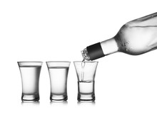 Pouring Cold Vodka Into Shot Glass On White Background