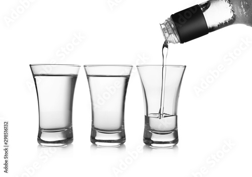Pouring cold vodka into shot glass on white background Wallpaper Mural