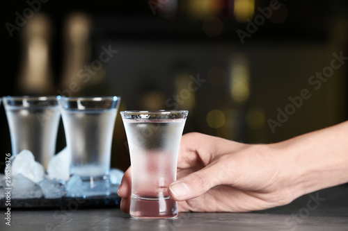 Woman with shot of vodka at table in bar, closeup Fototapeta