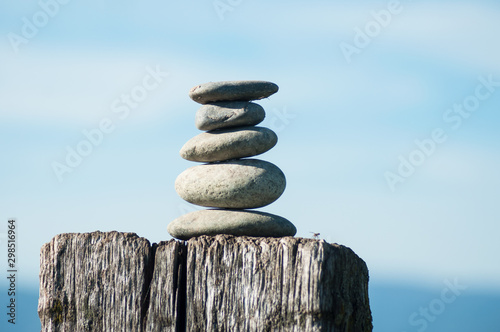Poster de jardin Zen pierres a sable Closeup of stone balance on wooden fence on blue sky background