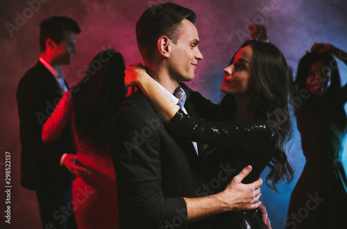 Falling in love. Gorgeous couple of smartly dressed man and a woman in black glittery dress is dancing in the dark, looking into each other's eyes and smiling. - 298522137