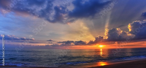 Phuket beach sunset, colorful cloudy twilight sky reflecting on the sand gazing at the Indian Ocean, Thailand, Asia.