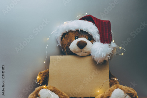 Fototapeta  Christmas card with Teddy bear holding a place for text and other Christmas decor light garland