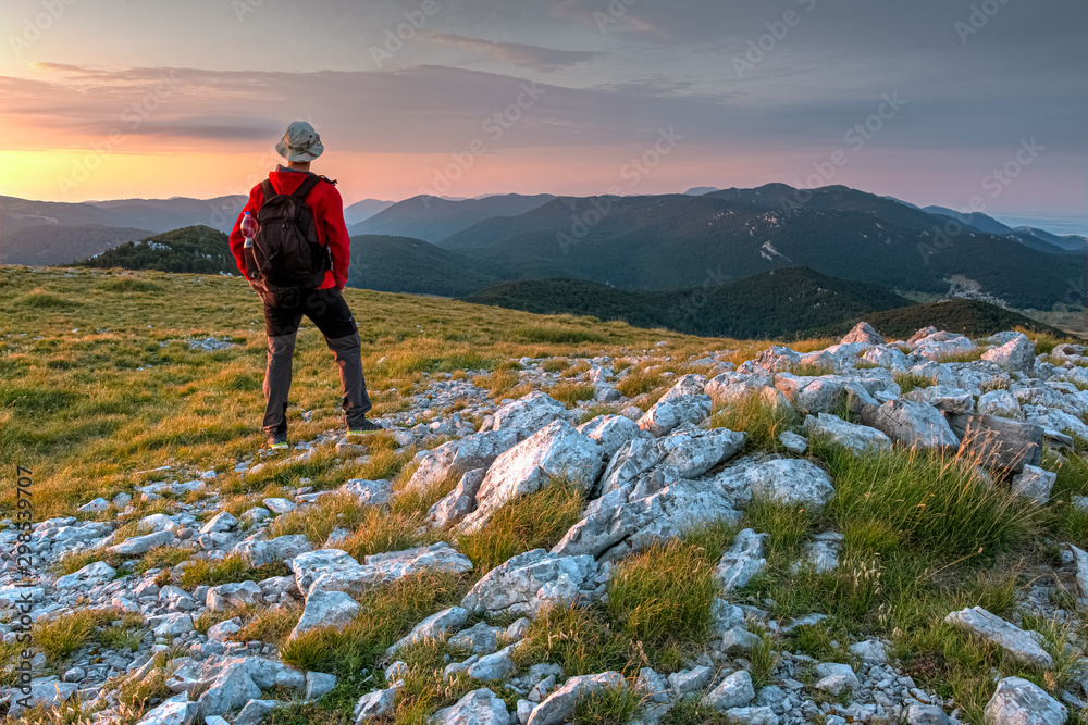 Fototapety, obrazy: The mountaineer standing on the top of the Alancic mountin in the Velebit mountain range photographing with the phone, Croatia