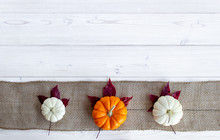Orange And White Pumpkins On Burlap With White Wood Background