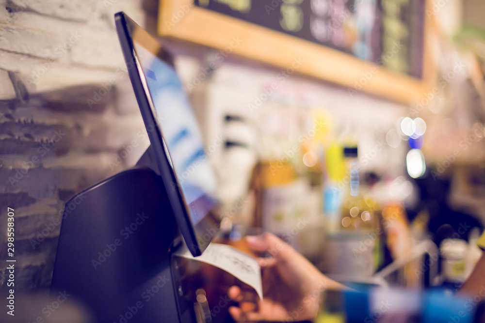 Fototapeta Blurry picture of cashier is printing receipt with cash register machine in cafe or store. Saleswoman receiving payment from customer in cafe or store. Blurry image for business background.