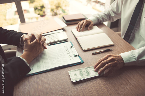 Photo Partner has made a fraud in the contract of sale and being handed a cash and pen to the businessman signing the contract corruption bribery concept