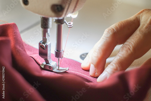 Carta da parati  Hand of the seamstress is using a white industrial sewing machine to sew cloth