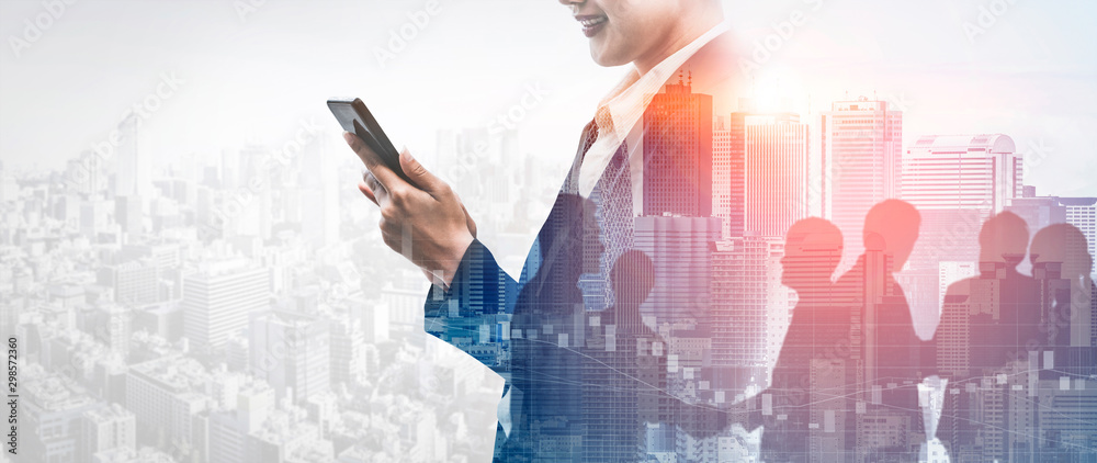Fototapeta Double Exposure Image of Business Communication Network Technology Concept - Business people using smartphone or mobile phone device on modern cityscape background.