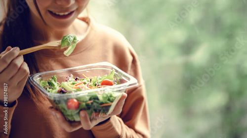 Fototapeta Closeup woman eating healthy food salad, focus on salad and fork. obraz