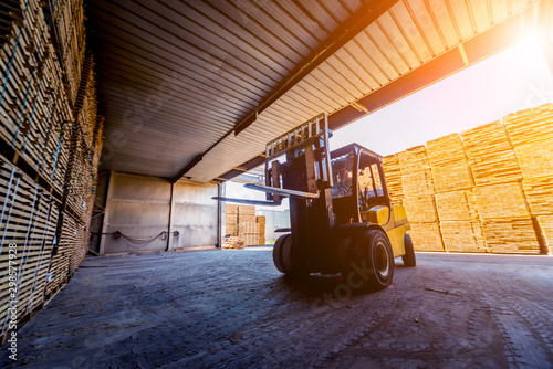 Obraz Forklift loader load lumber into a dry kiln. Wood drying in containers. - fototapety do salonu