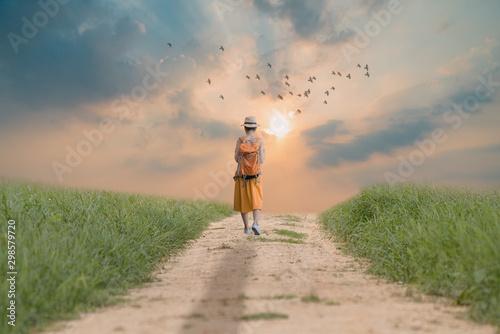 Fototapeta Alone young girl walking on the dirt road. obraz na płótnie