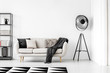 Leinwandbild Motiv Industrial black lamp next to beige couch with blanket and pillows, copy space on empty white wall