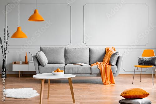 Obraz Orange lamp above grey scandinavian sofa in modern interior - fototapety do salonu
