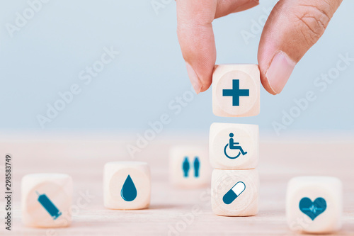 Tuinposter Apotheek Hand chooses a emoticon icons healthcare medical symbol on wooden block , Healthcare and medical Insurance concept