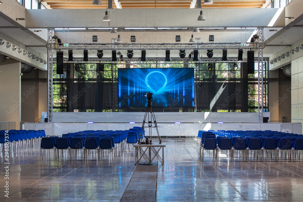 Fototapeta Empty Conference Room Equipped with Stage, Lights, Chairs and Professional Camera
