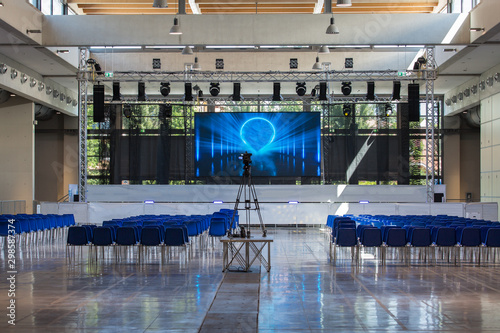 Obraz Empty Conference Room Equipped with Stage, Lights, Chairs and Professional Camera - fototapety do salonu