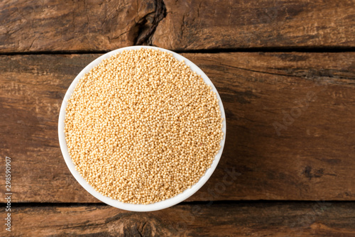 Amaranth seeds in bowl on rustic wooden table. Top view Canvas Print