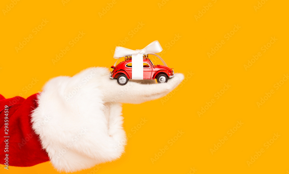 Fototapety, obrazy: Santa Claus holding modern car with bow in hand over orange