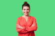 canvas print picture - Portrait of cute positive young woman with bun hairstyle, big earrings and in red blouse standing with crossed arms, kind look and charming smile. indoor studio shot isolated on green background