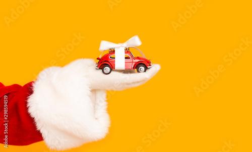 Fototapeta  Santa Claus holding modern car with bow in hand over orange