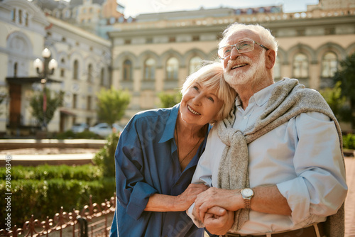 Fototapeta We love to travel together. Happy senior couple bonding to each other and smiling while standing outdoors obraz