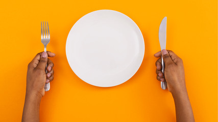 Empty plate and cutlery in woman's hands on orange background
