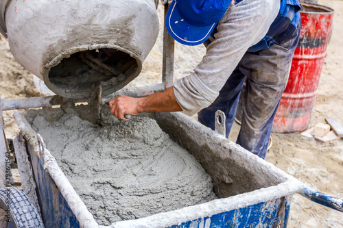 Tablou Canvas Worker is pour mortar in wheelbarrow