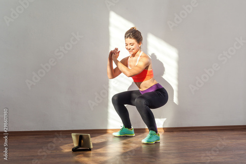 Fotomural Positive sportive woman with bun hairstyle and in tight sportswear doing squatting sit-up exercise while watching training video on tablet