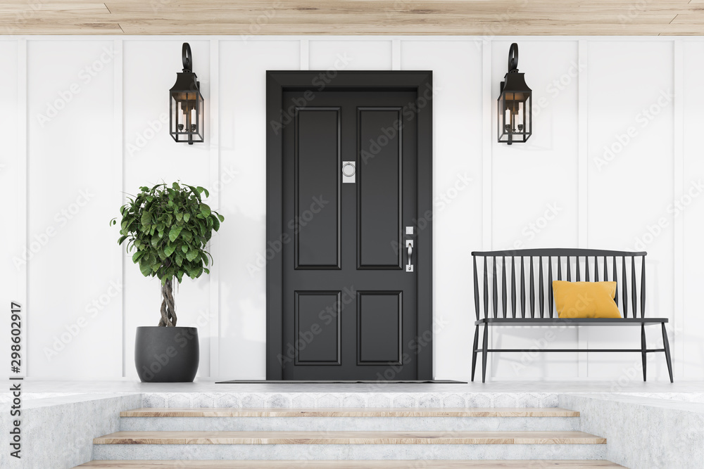 Black front door of white house, tree and bench