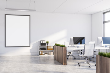 White office with dark wooden tables and poster